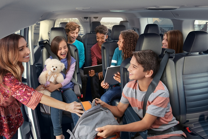 The interior of a 2020 Transit Passenger Van is shown with six passengers and a woman leaning in the open side door