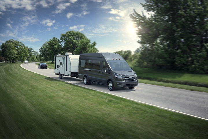 A 2020 Ford Transit towing a medium sized camper