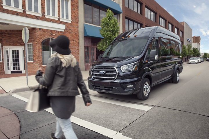 A woman walking infront of a 2020 Ford Transit stopped at an intersection