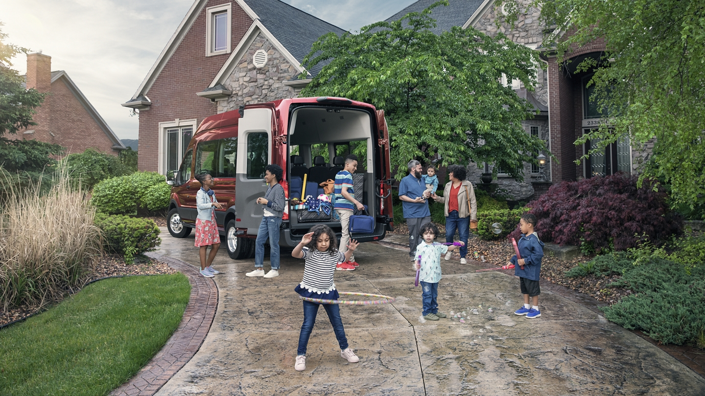 A group of kids playing near a 2020 Ford Transit with open cargo door