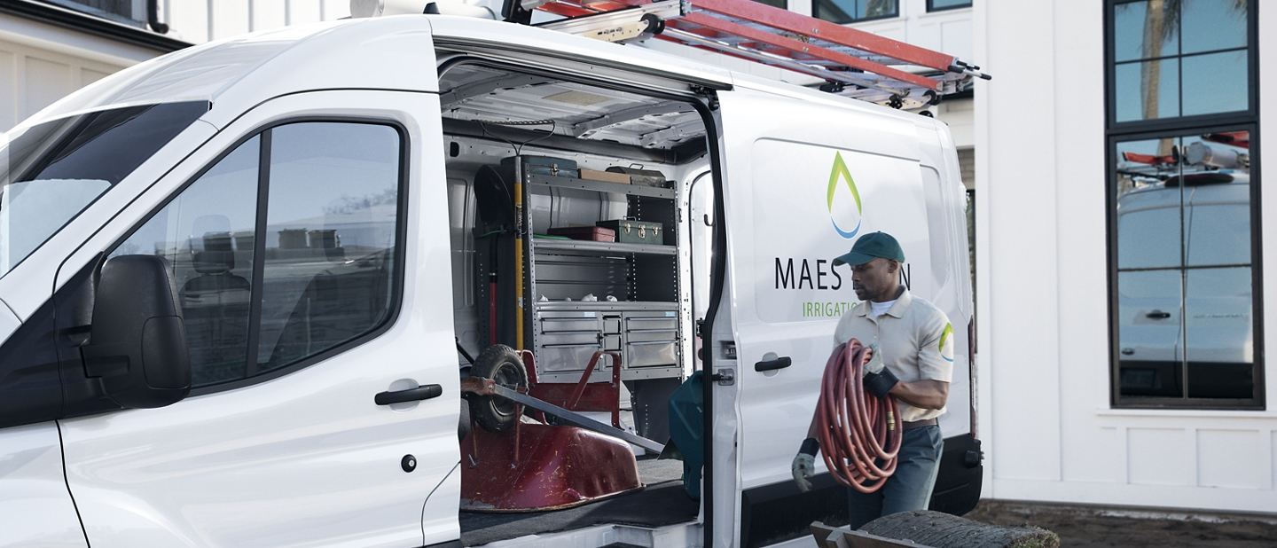 A man holding a hose working out of a 2020 Ford Transit