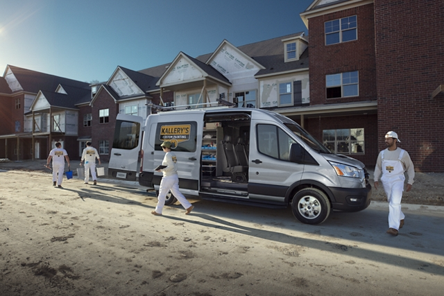 A work crew walking away from a 2020 Ford Transit at a construction site
