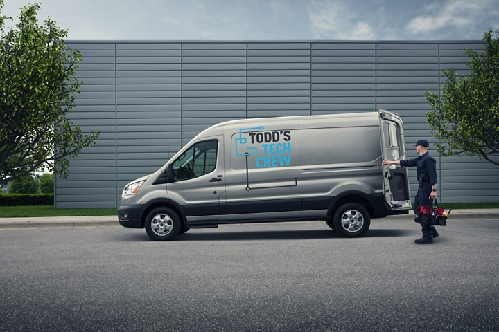 A worker opens the cargo door of a 2020 Ford Transit in Iconic Silver