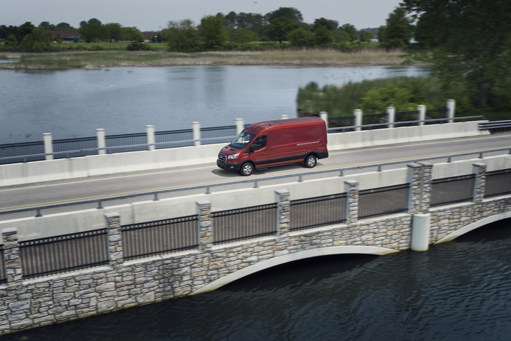 A 2020 Ford Transit in Kapoor Red being driven across a bridge