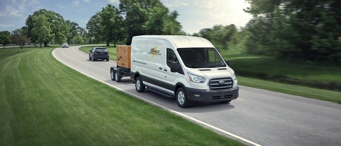 A 2020 Ford Transit towing a portable industrial generator