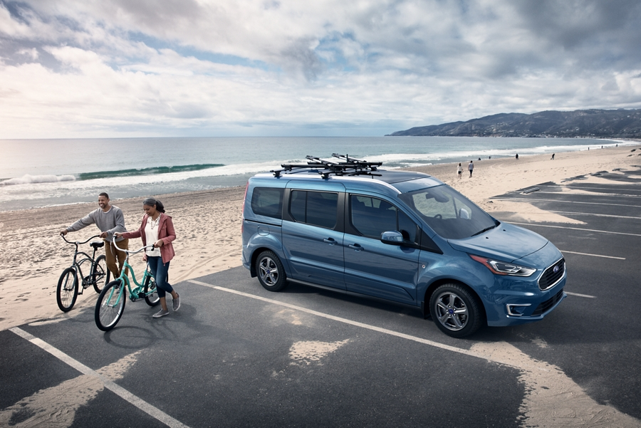 2020 Ford Transit Connect Passenger Wagon at the beach with available roof rack and two people walking their bicycles near it