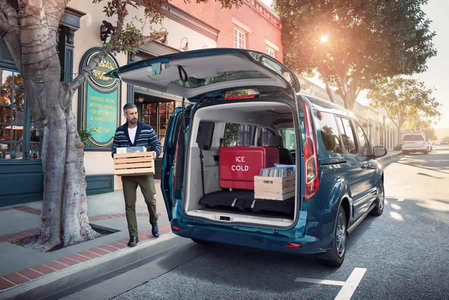 Man loading up a 2020 Ford Transit Connect Passenger Wagon through the rear door
