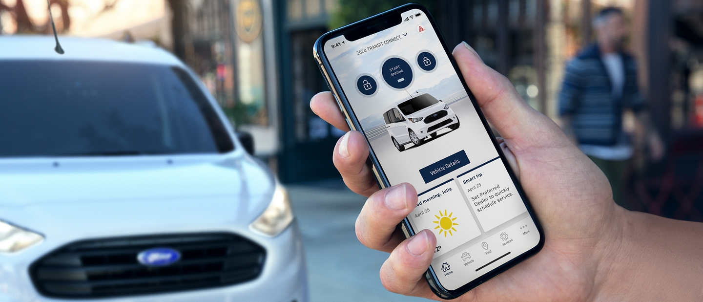 A hand holds a smartphone displaying a Transit Connect van within the FordPass App