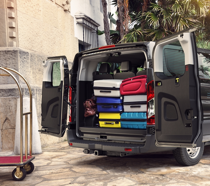 A resort bellhop unloads luggage from a transit passenger van
