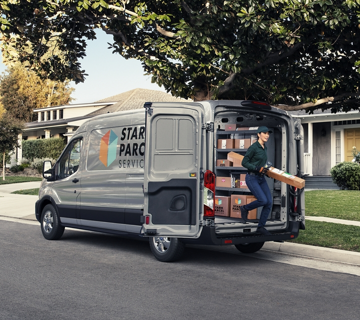 A delivery person emerges from the cargo area of a transit cargo van