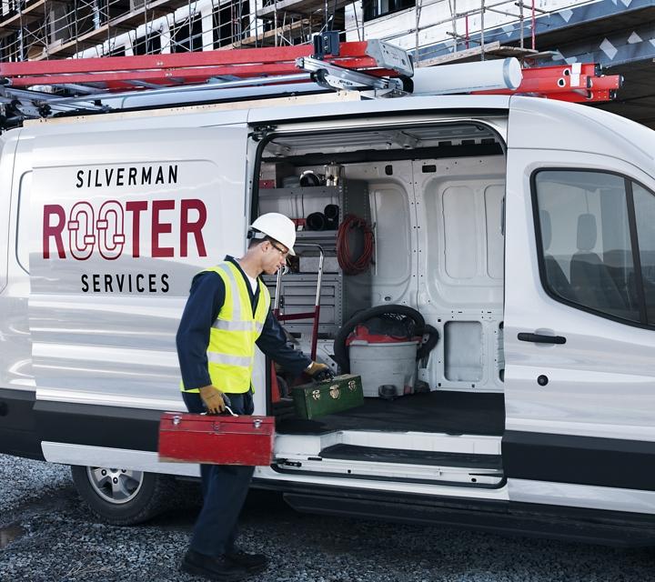 A plumber loads a toolbox onto a transit cargo van