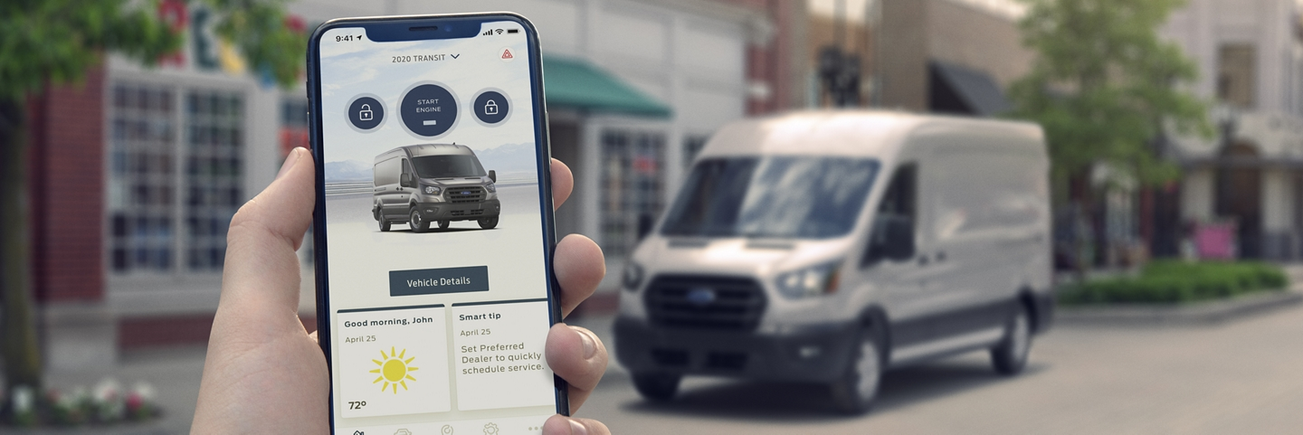 A hand holds a smartphone displaying a 2020 Ford Transit van within the FordPass App