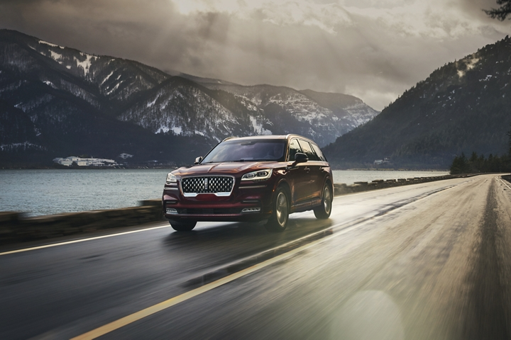 A Lincoln Aviator is shown being driven along a road in a breathtaking river valley