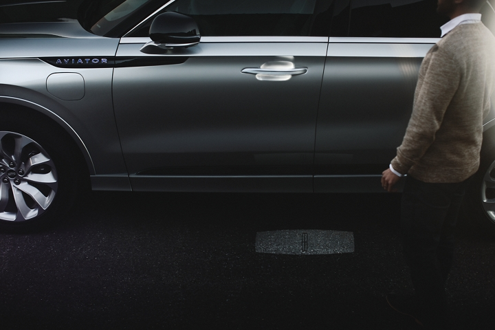 A person approaches a Lincoln Aviator Grand Touring as the Lincoln embrace sequence of welcome lighting illuminates