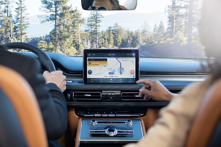 The front passenger is shown interacting with the waze app in the center screen of the Lincoln Aviator