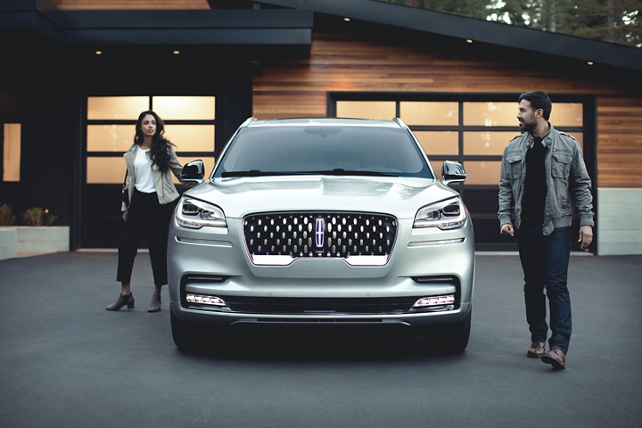 A couple is shown leaving a Lincoln Aviator Grand Touring model in the driveway of a modern home