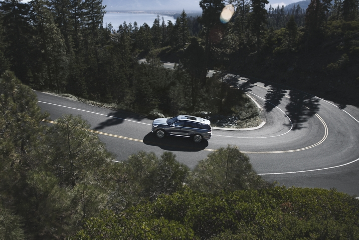 A Lincoln Aviator is shown from above as it traverses a winding mountain road