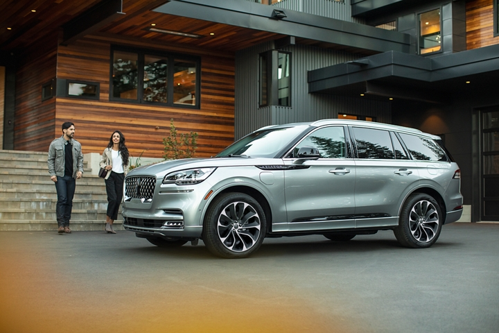 A couple approaches a Lincoln Aviator Grand Touring hybrid model that is parked in the driveway of a modern home