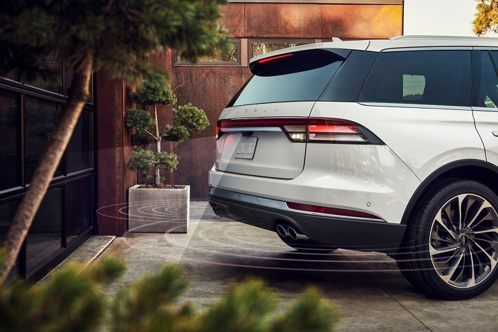 A Lincoln Aviator is shown as it is backing up dangerously close to a garage door