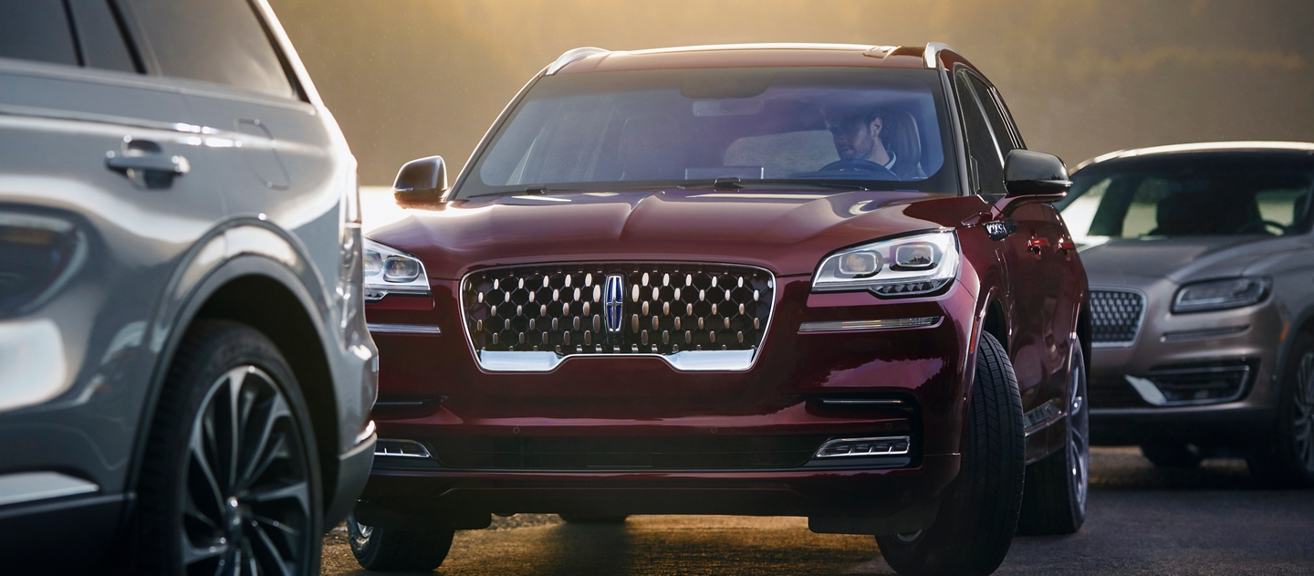 A Lincoln Aviator is shown using the active park assist plus system to park itself between two other vehicles