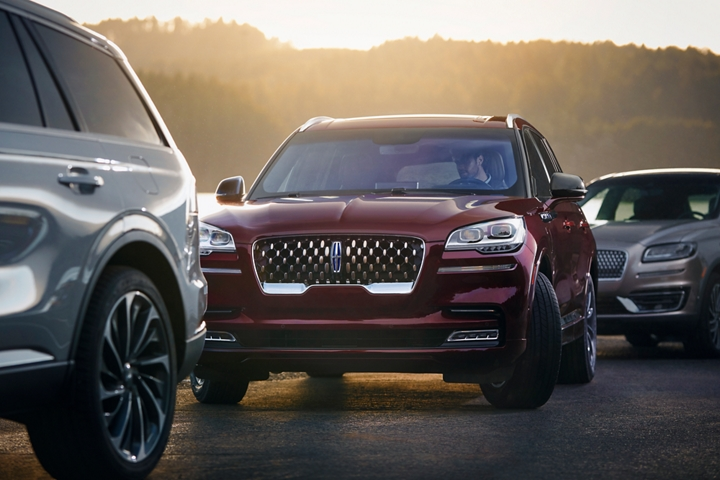 A Lincoln Aviator is shown as the vehicle parks itself between two other vehicles
