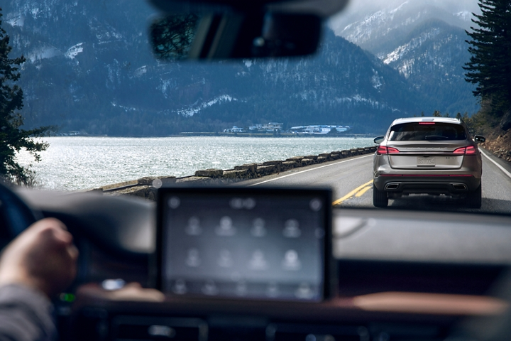 A vehicle that is rapidly braking is shown through the windshield of a Lincoln Aviator