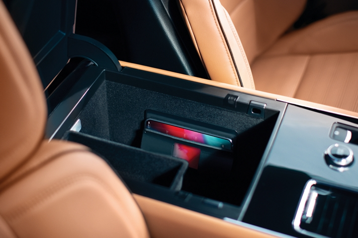 The front armrest storage bin is shown open with a phone clipped into the wireless charger