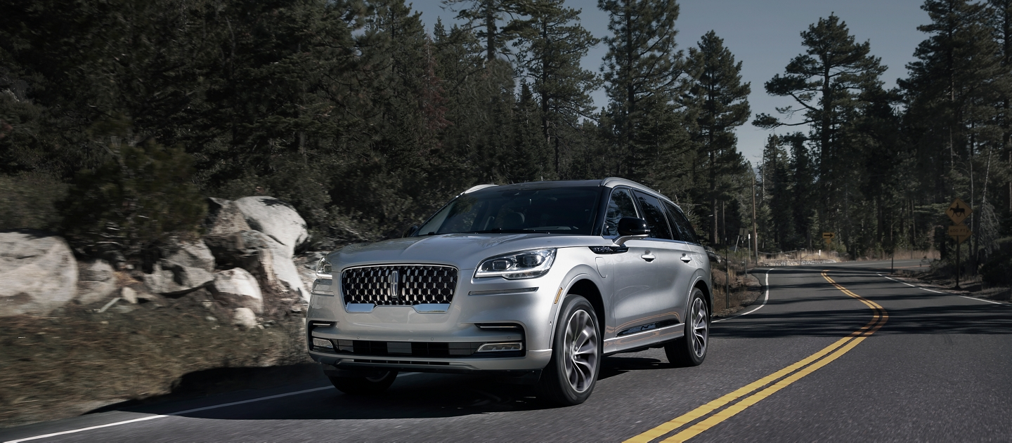 A Lincoln Aviator Grand Touring is shown being driven on a winding mountain road