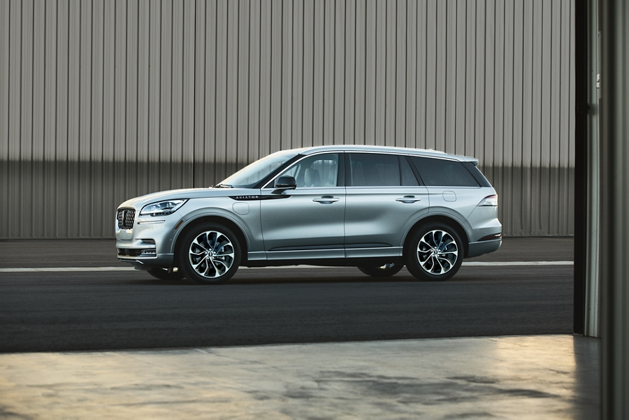 A Lincoln Aviator Grand Touring in the silver radiance exterior color is shown parked next to an airplane hangar