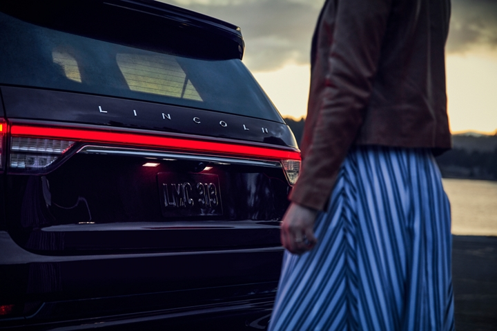 A woman is shown near the rear of a Lincoln Aviator as the Lincoln Embrace illuminates the rear lights