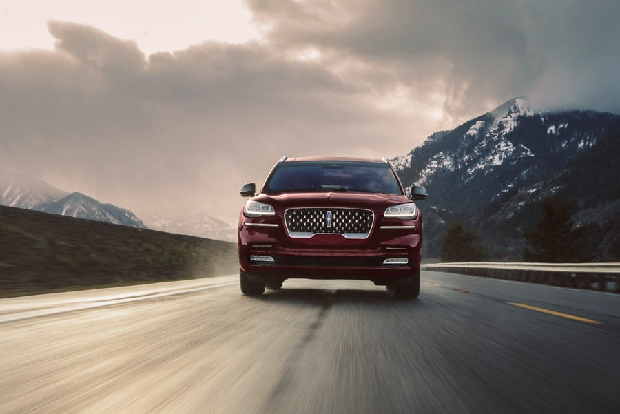 A Lincoln Aviator Grand Touring in the Burgundy velvet exterior color is shown being driven on a breathtaking river valley road