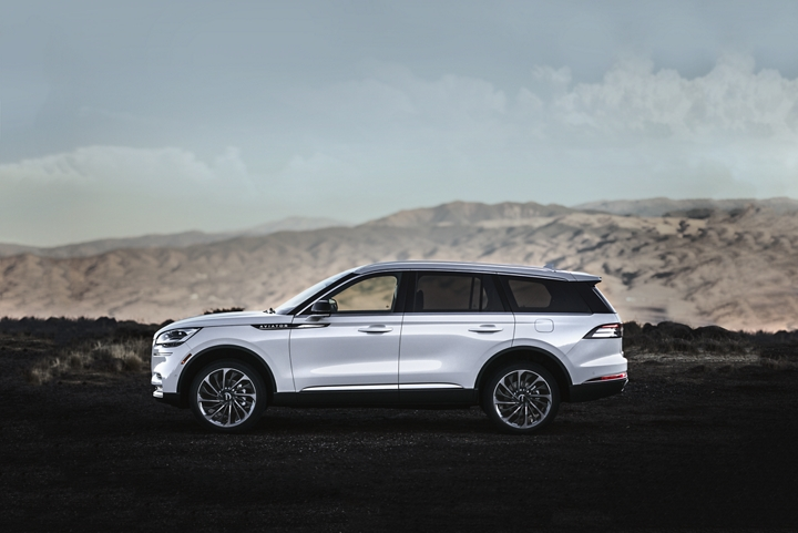 A Lincoln Aviator in the Pristine White exterior color is shown parked at a scenic mountain overlook