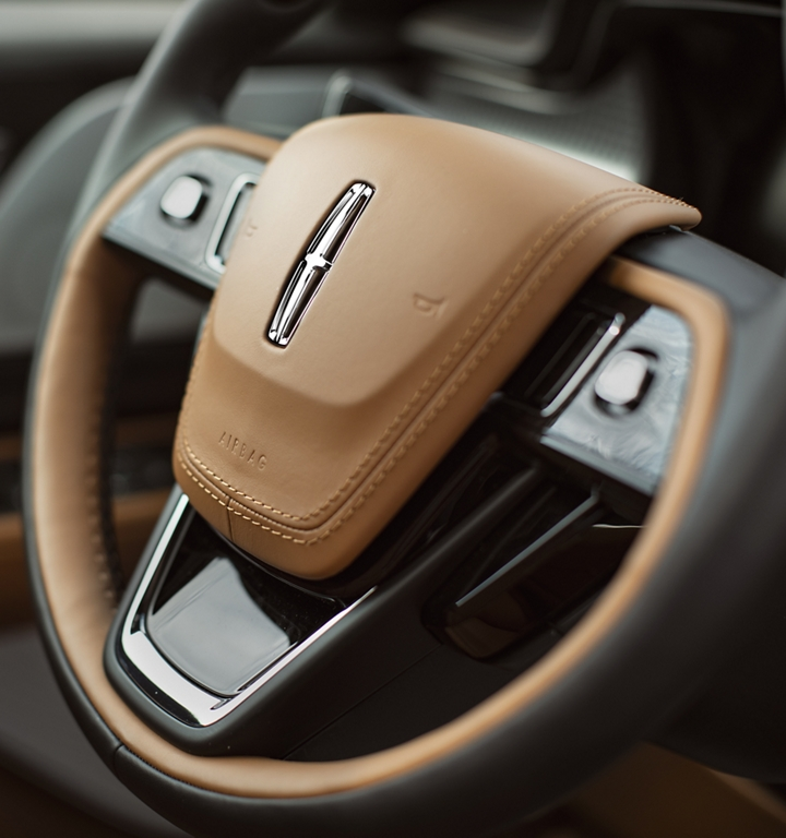 A detail shot of a steering wheel shows off the rich leather and high design details of a Lincoln Aviator Black Label theme interior