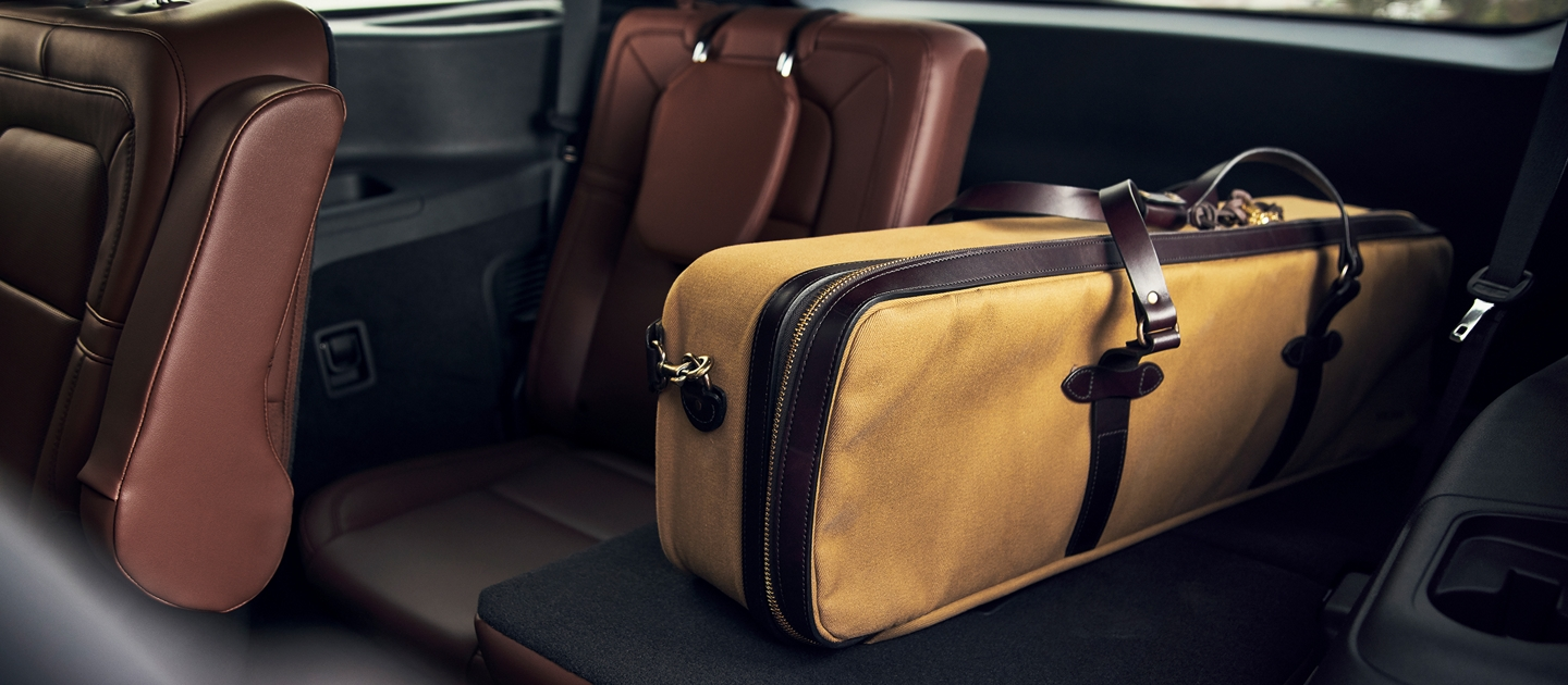 A large oblong bag is shown resting on one of the third row seats that have been folded flat