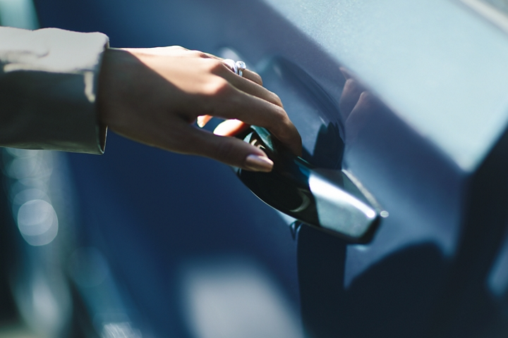 A hand gracefully grips the Light Touch door handle to demonstrate its ease of use