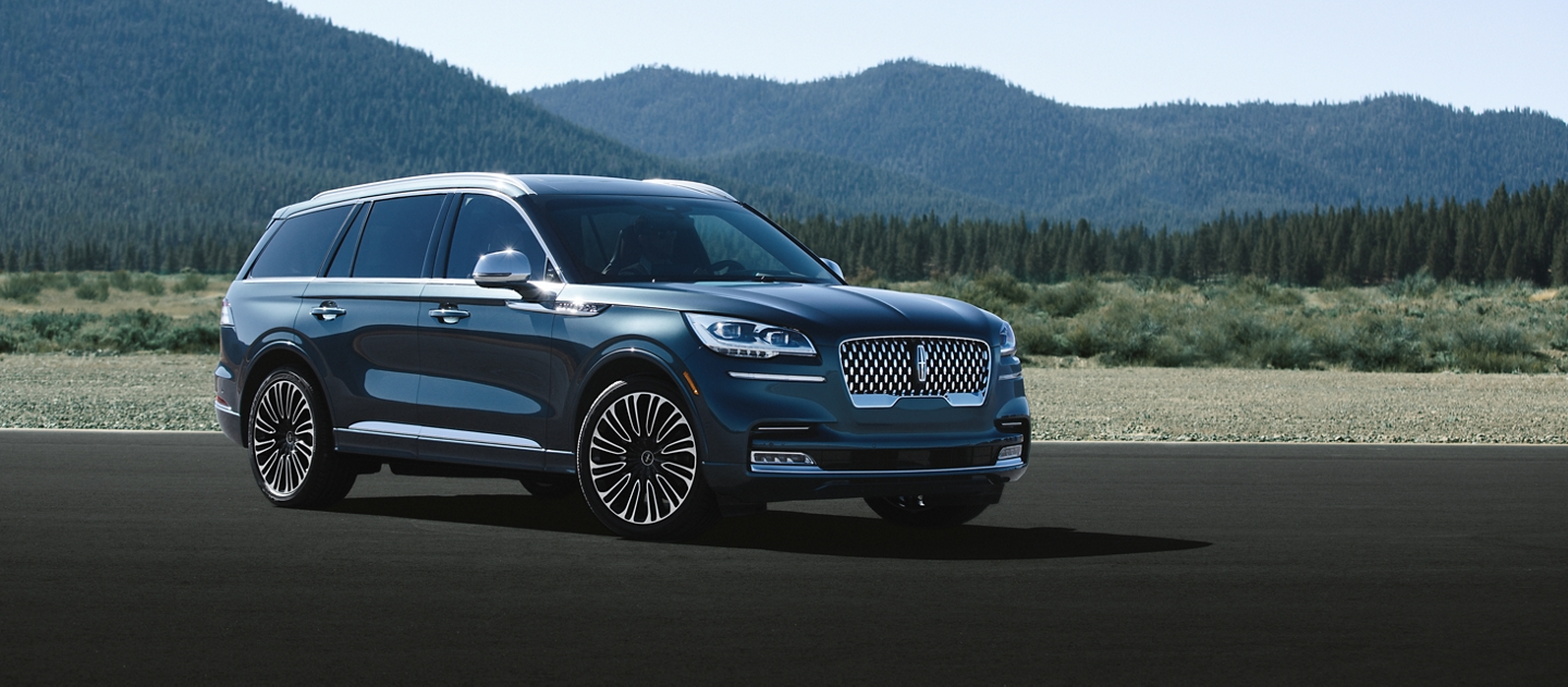 A 2021 Lincoln Aviator Black Label shown in the Flight Blue exterior color is parked on pavement with mountains in the background