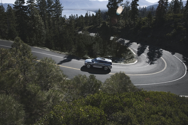 A 2021 Lincoln Aviator is shown from above as it traverses a winding mountain road