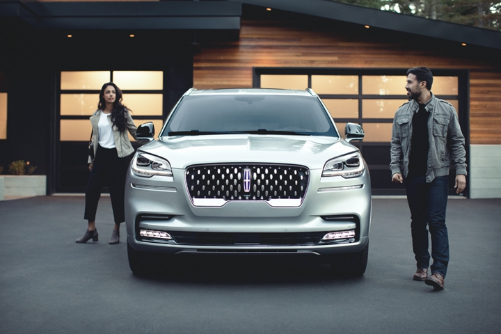 A couple is shown leaving a 2021 Lincoln Aviator Grand Touring model in the driveway of a modern home