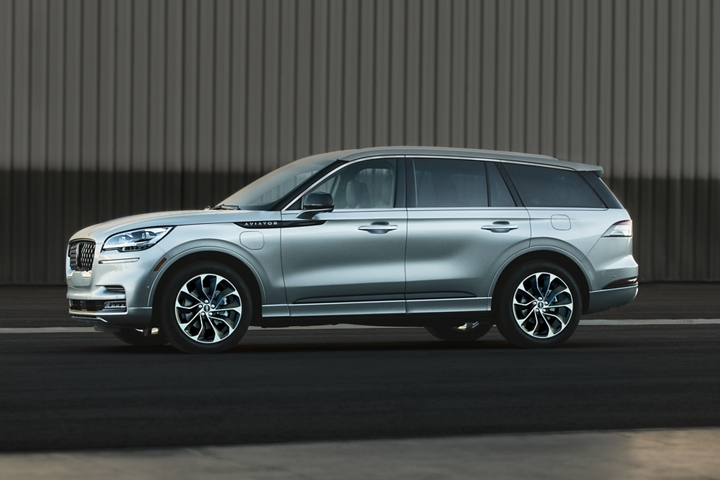 A 2021 Lincoln Aviator is shown parked next to a private airplane hangar