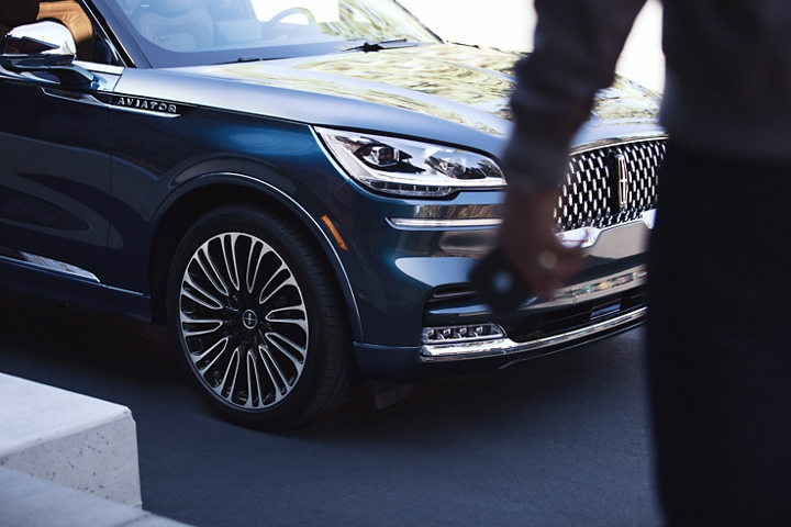 A man is shown approaching a 2021 Lincoln Aviator with his phone in his hand which can act as a key to the vehicle