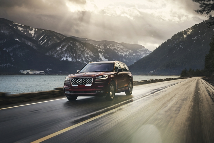 A 2021 Lincoln Aviator is shown being driven along a road in a breathtaking river valley