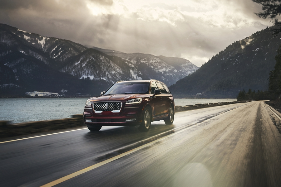 A 2021 Lincoln Aviator is shown being driven on a road in a breathtaking river valley