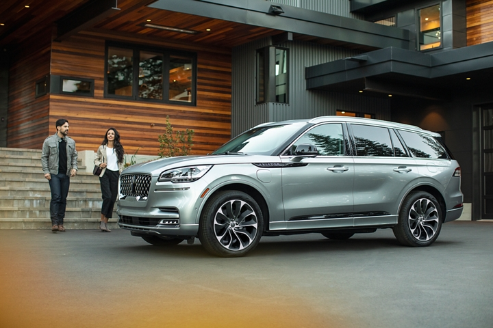 A couple approach a 2021 Lincoln Aviator Grand Touring model that is parked in the driveway of a modern home