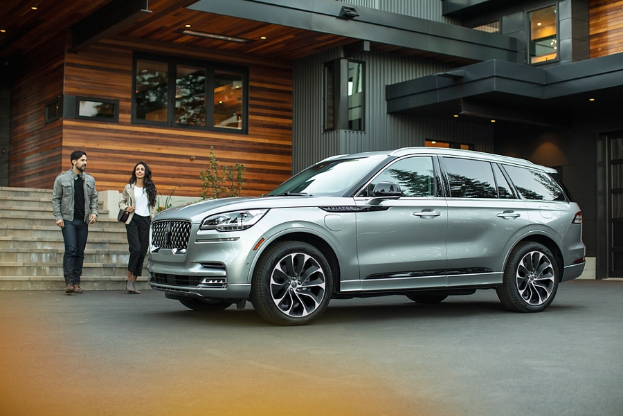 Two people are shown approaching a 2021 Lincoln Aviator Grand Touring model that is parked in the driveway of a modern home