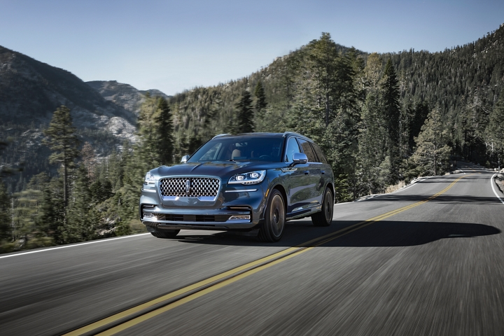 A 2021 Lincoln Aviator Black Label is shown being driven on a mountain road where all wheel drive could be helpful