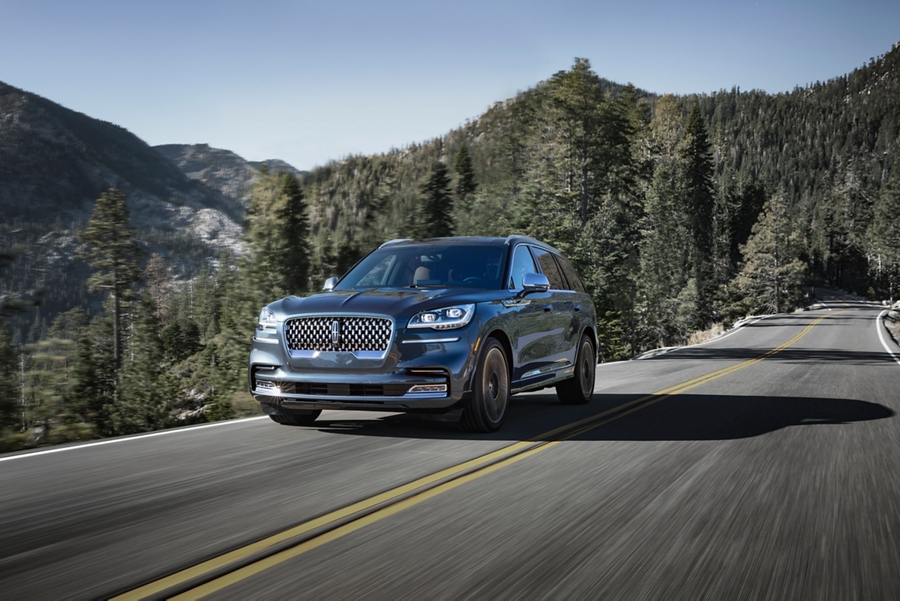 A 2021 Lincoln Aviator is shown being driven on a tree lined mountain road