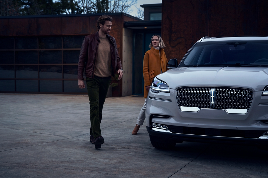 A man and a woman are shown approaching a 2021 Lincoln Aviator which illuminates certain lights when they are close