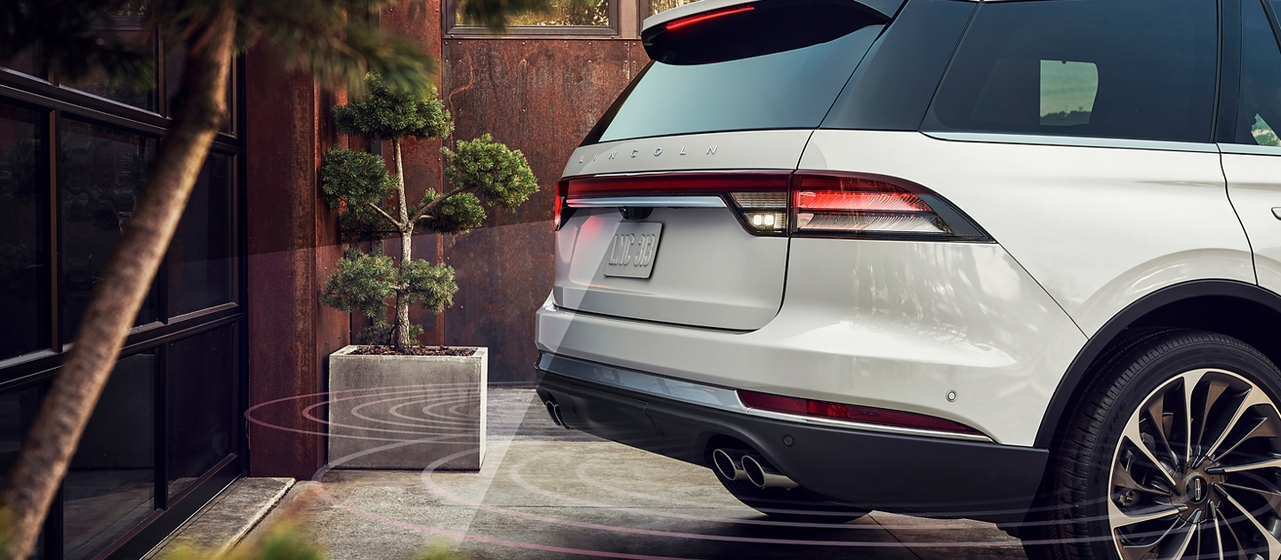 A 2021 Lincoln Aviator is shown as it backs up toward a garage with lines representing the radar technology used to help prevent a collision