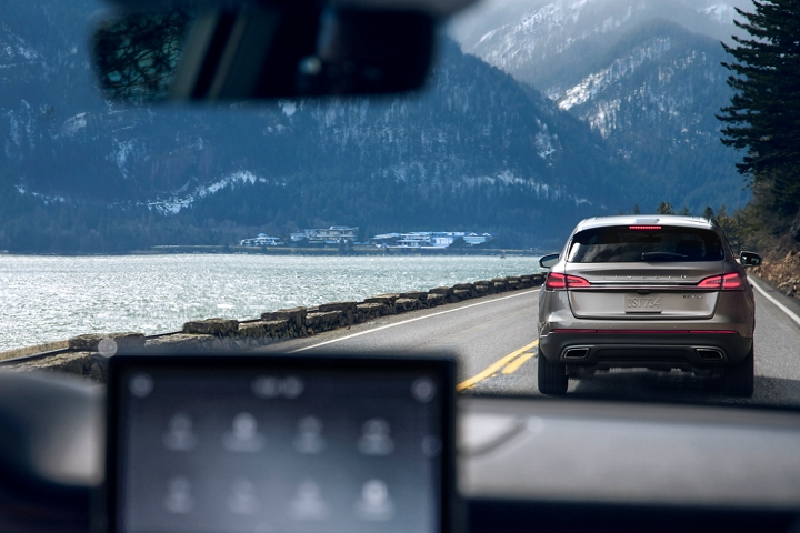 A vehicle that is rapidly braking is shown through the windshield of a 2021 Lincoln Aviator