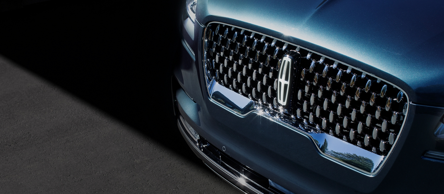 The 2021 Lincoln Aviator Black Label grille is shown with raised Lincoln star logo like shapes surrounding the center Lincoln emblem